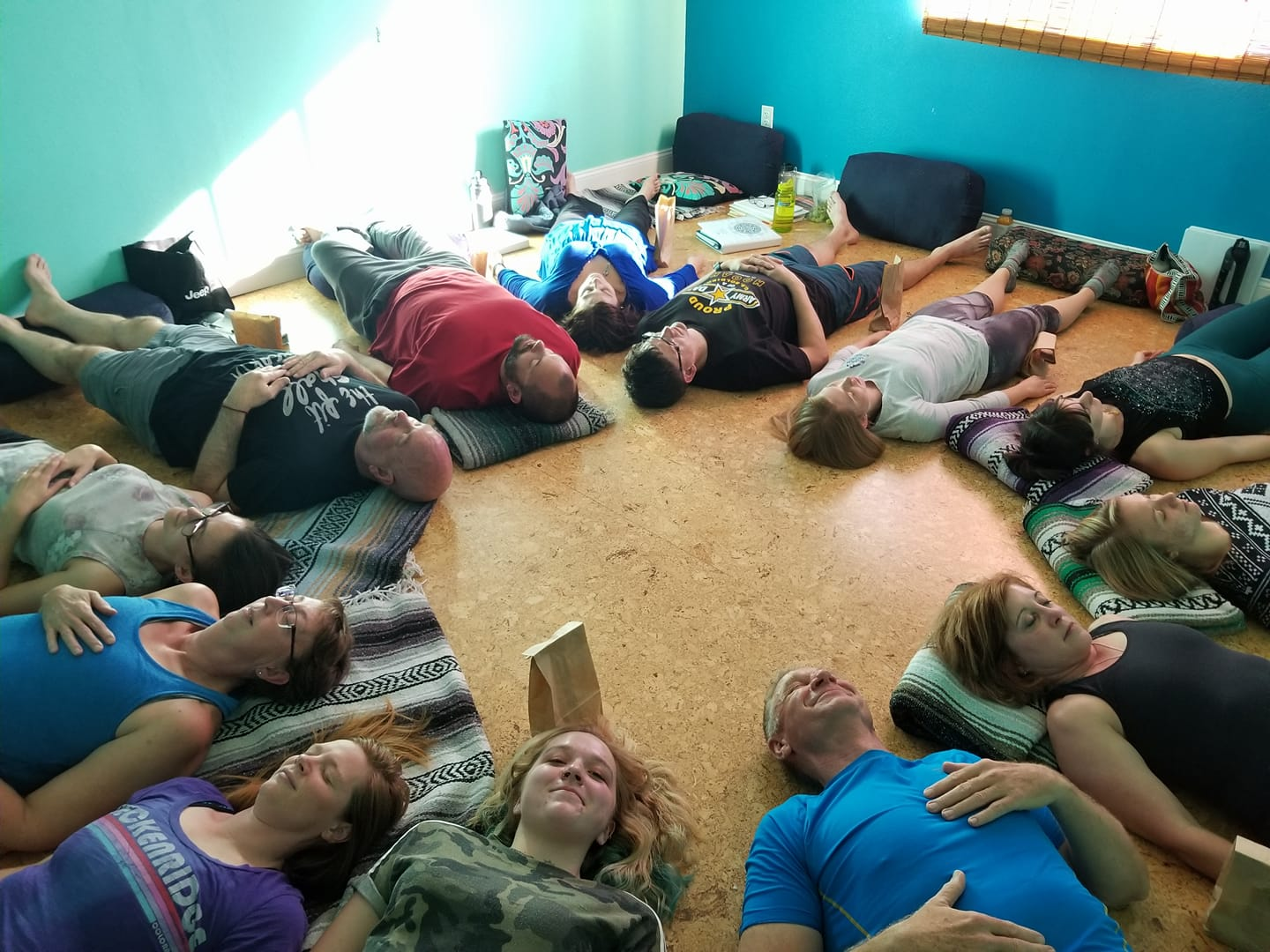 Group of students laying with heads facing middle in a circle